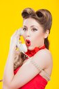Pin up girl talking on retro telephone yellow background Stock Photo