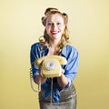 Pin up hotline phone operator call us adorable female pinup model holding olden day rotary in a now concept on yellow gradient Stock Images