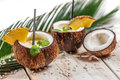 Pinacolada in the coconut with pineapple on old wooden table Royalty Free Stock Images