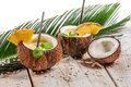 Pinacolada in the coconut with pineapple on old wooden table Royalty Free Stock Photos