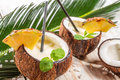 Pinacolada drink with mint served in a fresh coconut on old wooden table Stock Photo