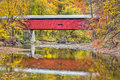 Pine bluff covered bridge autumn foliage surrounds reflected in the waters of putnam county indiana s big walnut creek Stock Photo