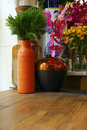 pine tree leaf in pottery vase on wood table and flowers Royalty Free Stock Photo