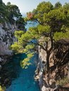 Pine trees on a rock over crystal clear turquoise water near Cape Amarandos at Skopelos island Royalty Free Stock Photo