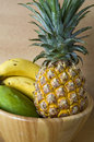 Pineapple banana mango tropical fruits wooden bowl Stock Image