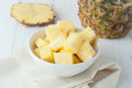 Pineapple chunks in white bowl on yellow napkin with pieces at the background Stock Images