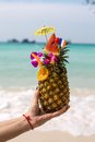 Pineapple coctail in a woman s hand infront of the sea Stock Photos