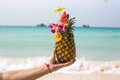 Pineapple coctail in a woman s hand infront of the sea Stock Images