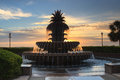 Pineapple fountain waterfront park downtown charleston south carolina backlit against rising sun creating golden glow water Royalty Free Stock Photo