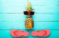 Pineapple with glasses and slippers on blue wooden background. Copy space and top view Royalty Free Stock Photo