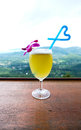 Pineapple juice in glass and blue heart shape straw with cityscape of samui island thailand Royalty Free Stock Images