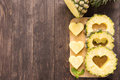 Pineapple slices with a cut in the shape of hearts on wooden bac Royalty Free Stock Photo