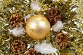 Pines cones, feather and golden Christmas ball on a golden tinse Royalty Free Stock Photo