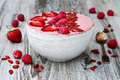 Pink acai, maca powder smoothie bowl topped with sliced strawberries, raspberries and goji berries. Royalty Free Stock Photo