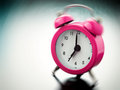 Pink alarm clock ringing on bedside table Stock Photos