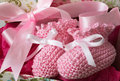 Pink baby booties knitted with ribbon gift bow Royalty Free Stock Images
