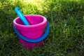 Pink baby bucket and blue shovel Royalty Free Stock Photo