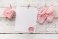 Pink baby's booties. Small girls sock, blank card with wax seal and present box on white wooden background Royalty Free Stock Photo