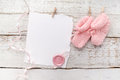 Pink baby's booties. Small girls sock and blank card with wax seal on white wooden background Royalty Free Stock Photo