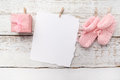 Pink baby's booties. Small girls sock and blank card on white wooden background Royalty Free Stock Photo