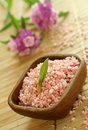Pink bath salt in wooden bowl and pink flowers. Royalty Free Stock Photo
