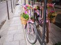 Pink bicycle decorated with flowers leans against a shop window Royalty Free Stock Photo