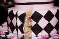 Pink and black specialty cake with a slice cut out rose petals around the base Stock Photo