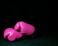 Pink boxing gloves sitting dark Stock Photo