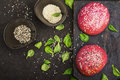 Pink buns for the vegetable Burger on the basis of beet with sesame seeds on dark background. Top view Royalty Free Stock Photo
