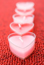 Pink candles in form of heart five on red background Royalty Free Stock Photography