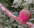 Pink christmas scene snow falling on ornaments and tinsel Stock Photo