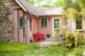 Pink cottage porch a small is nestled in the side of a rustic stucco Royalty Free Stock Photos