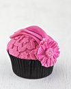 Pink cupcake couture with embossing and flower in fondant icing Stock Photos