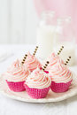 Pink cupcakes decorated with stripey chocolate straws Royalty Free Stock Photography