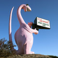 Pink dinosaur holding sign Stock Image