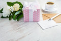 Pink dotted gift box, empty greeting card, kraft envelope, peonies bouquet and coffee cup over white wooden rustic table. Romantic