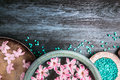 Pink flowers in bowls with water and blue sea salt on wooden table wellness background top view place for text Stock Image