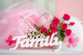 Pink flowers and family sign still life with wooden delicate roses in colors Stock Image