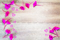 Pink flowers formed as border with hearts on vintage grunge wooden background Royalty Free Stock Photo