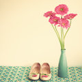 Pink flowers and girly shoes in a blue vase with Stock Image