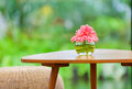 Pink flowers in vase on table in the garden Royalty Free Stock Photo