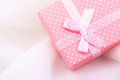 Pink gift box tied with satin ribbon with bow on delicate white fabric background, romantic, valentine, mother`s day, Christmas