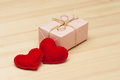 Pink gift box and two hearts felt on wood background Royalty Free Stock Images