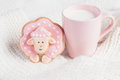 Pink gingerbread sheep with cup of milk on white knitted backgro background pastel colored Stock Photo