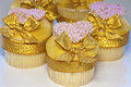 Pink and gold cupcakes iced cup cakes decorated with golden bows hearts Stock Photo