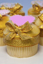 Pink and gold cupcakes iced cup cakes decorated with golden bows hearts Stock Photography