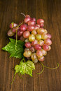 Pink grapes with leaves on a wooden background Royalty Free Stock Images