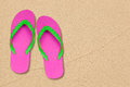Pink and green flip flops on the beach Stock Photo