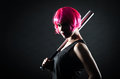 Pink haired girl with bat woman hair holding a baseball in front of a patterned background Royalty Free Stock Photos