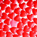 Pink heart between a pile of red hearts candy hearts background concept standing out from the crowd Stock Images